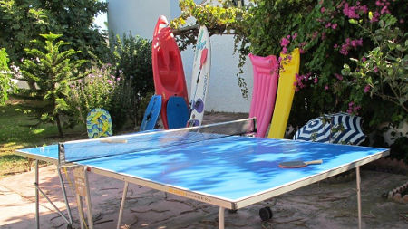 Free time activities in the hostel. In the photo: table tennis, surfboard, air mattress and sunshade